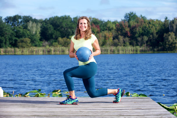 Debbie Ivie holding a medicine ball in a twisted lunge position on a dock by the lake.
