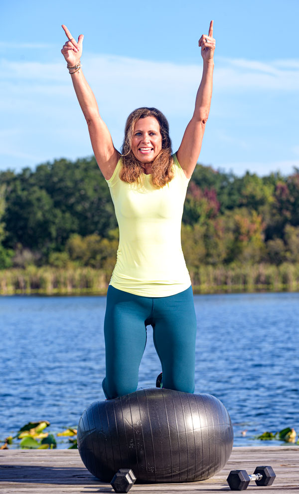 Debbie Ivie of Fit Rx Performance balancing on her knees with arms in the air on top of a balance ball on a dock at the lake.