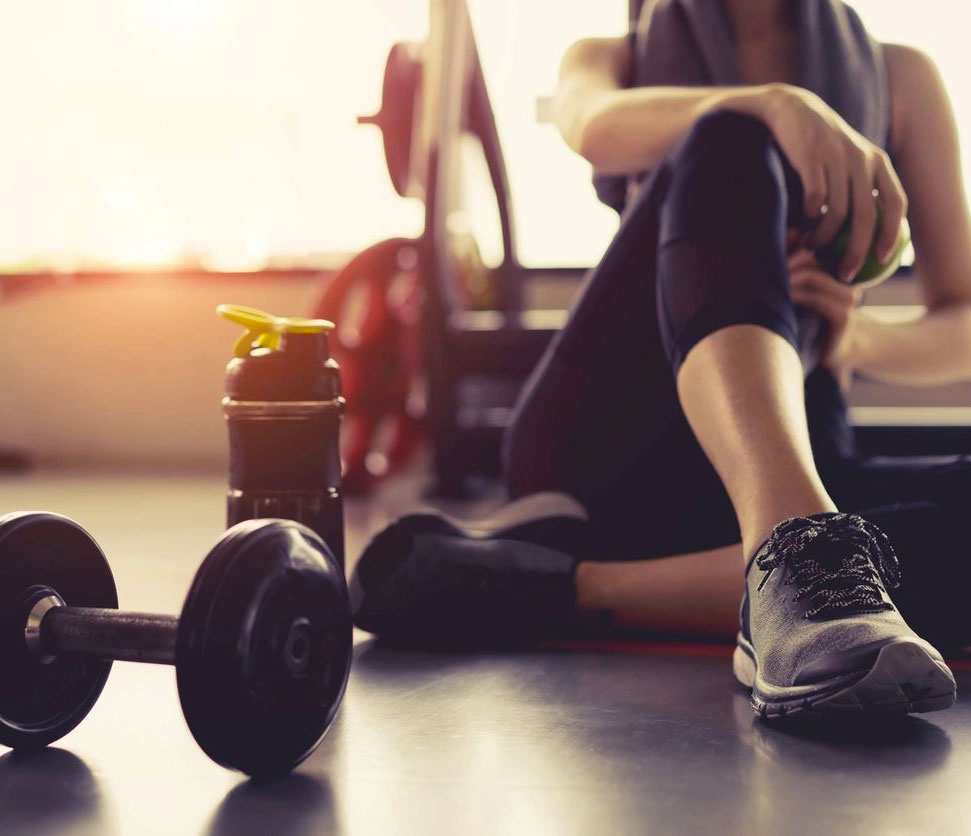 Girl in gym sitting down on the floor with a water bottle and dumbbell nearby.
